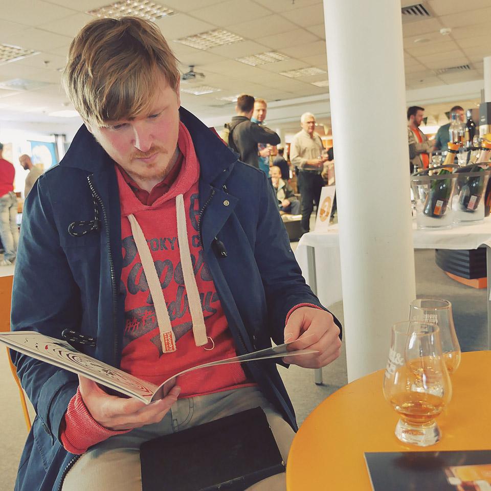Gute Vorbereitung ist Trumpf: Malt Whisky-Redakteur Samuel stöbert beim Whisky-Festival auf Fehmarn im Messekatalog (Foto: Malt Whisky)